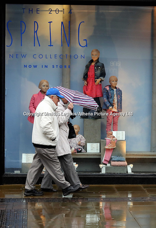 WEATHER PICTURE WALES<br /> Pictured: An elderly couple share an umbrella as they walk by a Spring Collection shop window in Oxford Street, Swansea, south Wales. Friday 14 February 2014<br /> Re: More strong winds have been forecast and severe flood warning issued for parts of the UK.
