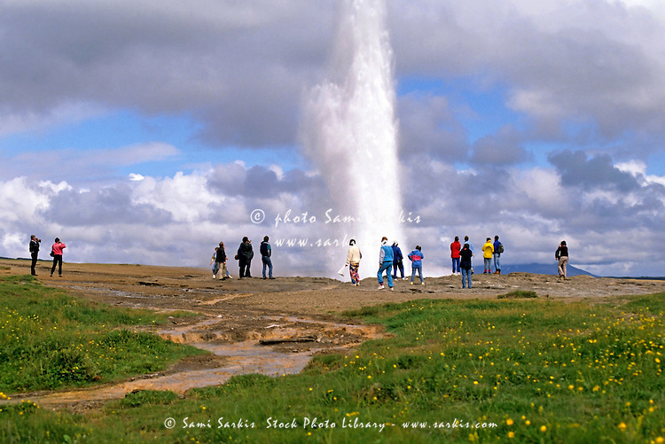 Tourists watching an eruption at Geysir, the earliest geyser known to Europeans, in the Haukadur valley, Iceland.