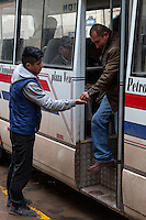 Peru, Cusco.  Young Man Collecting Fare from Disembarking Bus Passenger.
