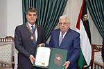Palestinian president Mahmoud Abbas honors Major General Hazem Atallah, in the West Bank city of Ramallah, on October 5, 2021. Photo by Thaer Ganaim