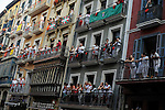 People on balconies watch participants running in front of Torrestrella's bulls during the fifth bull run of the San Fermín Festival in Pamplona, northern Spain on July 11, 2013. © Pedro ARMESTRE