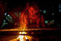 Mementoke Coba, a Waorani  (Huaroni) woman, starts a fire to cook bushmeat in the early morning.