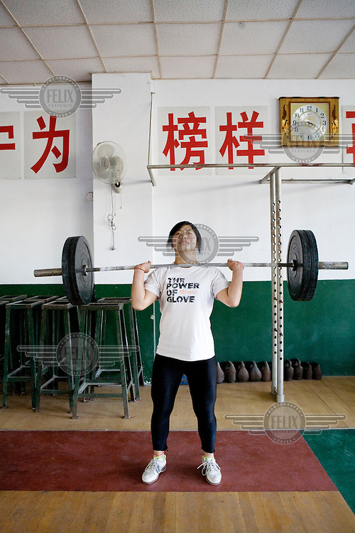 A student trains at the Weifang City Sports School, one of 3,000 state-run athletic academies that consign nearly 400,000 youngsters to a form of athletic servitude. In the category of weight-lifting most of these students come from farming communities. They have been hand picked by sports scouts who travel to far away provinces visiting schools whilst taking detailed measurements of potential atheletes. There is more of a focus on finding girls as research by the Chinese state suggests that it is easier to win Olympic gold medals in this area.They measure shoulder width, thigh length and waist circumference - and if everything fits, these young students are told they have the honour of serving their motherland.