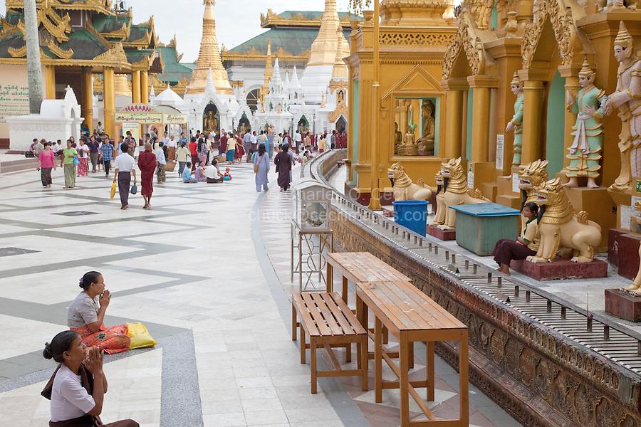 Myanmar, Burma.  Shwedagon Pagoda, Yangon, Rangoon.  Women Praying to Nats, Buddhist spirits worshipped in Maynmar, as Visitors Circumambulate the Stupa.