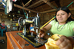 Mayan woman using peddle-sewing machine in her thatched hut in Midway village in southern Belize
