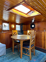 BNPS.co.uk (01202) 558833. <br /> Pic: Zeewarriors/BNPS<br /> <br /> Pictured: Dining area. <br /> <br /> A 100-year old Dutch sailing barge moored in Bermondsey has gone on sale for £278,000.<br /> <br /> The 25-metre MV Johanna Elisabeth was originally constructed in 1913 at Appelo, Zwartsluis in Holland, and was brought to the UK in 2003 by a previous owner.<br /> <br /> Her work as a sailing barge included shipping freight but she is now moored at the South Dock Marina in Bermondsey, south London, and used as a home.