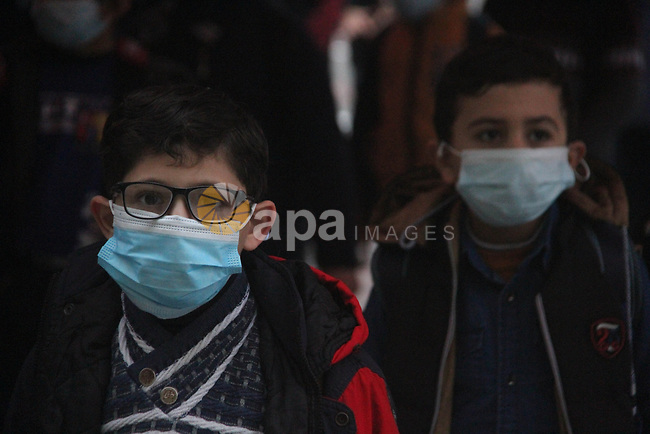 Palestinian students wearing protective face masks, participate in a morning activity as schools gradually reopen amid the coronavirus disease (COVID-19) outbreak, at their school in Gaza city on January 13, 2021. In a written statement, the Palestinian Health Ministry said 7 more people have died from the virus in the last 24 hours in Gaza strip and that 437 new cases have been identified. Photo by Mahmoud Ajjour