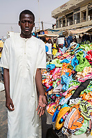 Senegal, Touba.  Young Man Selling an Assortment of Women's and Girls Clothing.