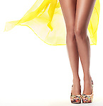 Sexy long legs of a young woman wearing yellow summer beach dress isolated on white background Image © MaximImages, License at https://www.maximimages.com