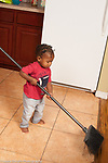 17 month old toddler boy using broom to sweep kitchen floor