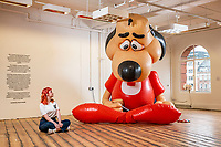 BNPS.co.uk (01202 558833)<br /> Pic: MaxWillcock/BNPS<br /> <br /> Pictured: There's an art gallery in the new Bobby's store. Gallery attendant Mise Maher sat beside 'Underdog', a giant, inflatable cartoon dog in a superhero costume created by American artist Chad Person<br /> <br /> The highly anticipated relaunch of Bobby and Co half a century after it closed could offer the blueprint for a department store renaissance.<br /> <br /> The grand Art Deco style building in the seaside town of Bournemouth, Dorset, will become a cultural hub hosting independent traders, a rooftop bar, and art gallery.  <br /> <br /> It originally housed one of the country's most well-known department stores until 1972 when Debenhams took it over.