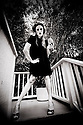 B&W photograph of model drinking wine standing on top of stairs.  Wearing thrift store vintage fashion. Retro. Reduce, Reuse, REcycle, Refashion.  Photography by Liisa Roberts