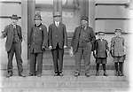COURTHOUSE DENIZENS, C. 1915. The north steps of the post office are the setting for this group portrait, which includes a policeman and two newsboys. Mirrored in the glass doors is a sign for Deluxe Studio, a photographer's establishment north across P Street from the courthouse. John Johnson's care in composing images suggests he was probably aware of this reflection.<br /> <br /> Deluxe studio was owned by Gustav(e) Shelander. Shelander lived at 938 P--the studio--in 1913.  By 1917 he'd married Theckla and moved his studio to 1213 O St but they still lived at 938 P.<br /> The 1920 Census has them at 814 South Street, then later they had a bungalow on S. 27th St., just above H, and lived there for decades.<br /> <br />  They were both born in Sweden, he about 1875, emigrating in 1892; she in 1895, emigrating in 1902.<br /> <br /> Photographs taken on black and white glass negatives by African American photographer John Johnson  from 1910 to 1925 in Lincoln, Nebraska. Douglas Keister has 280 5x7 glass negatives taken by these photographers. Larger scans available on request.