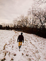 Man walking through snow covered field<br />