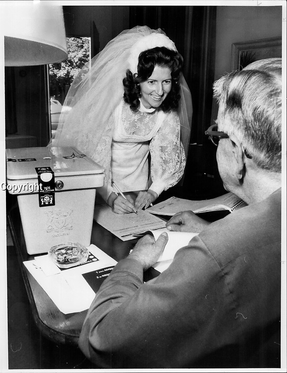 On her way to her wedding Saturday; Marilyn A. Keating stopped off at an advance poll on Deforest Rd. west of High Park. Poll clerk Jane Slinger gave her a ballot; she voted; and then went to St. Pius X Church to marry Sam Tornabuono. They'll be honeymooning in Quebec on election day. Advance polls are open today.<br /> <br /> 1975<br /> <br /> PHOTO :  Frank Lennon - Toronto Star Archives - AQP