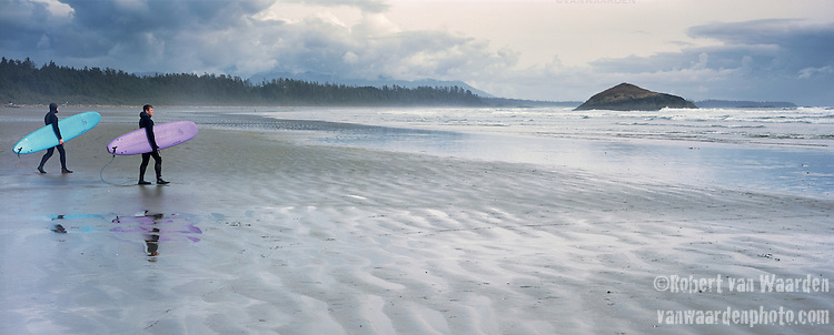 Two Surfers head out to test the waves on Long Beach, Vancouver Island..