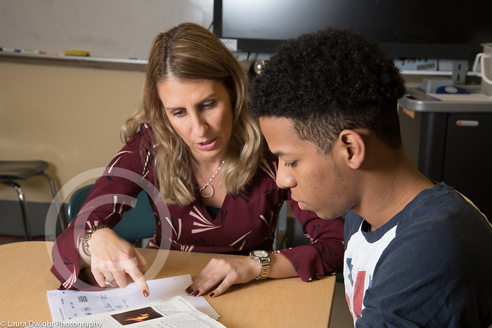 Education High School female teacher working with male student in the classroom