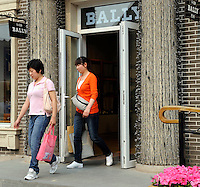 Chinese ladies leaves a Bally store at Beijing Scitech Premium Outlet Mall in Beijing, China. Opened in July 2009, Beijing Scitech Premium Outlet Mall is located in Beijing's most prestigious villa neighborhood. The outlet, featuring Colonial and Victorian architecture, the first of its kind in China, contains gallery of top-tier luxury brands, as well as showcases a wide selection of popular sports and leisure brands at discounted prices. .15 May 2010