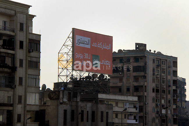 """A billboard reading """"participating in the constitution means YES for the 30th of June and the 25th of January"""" is seen in Cairo on December 17, 2013. The Islamist supporters of deposed Egyptian president Mohamed Morsi will boycott a referendum on a new constitution next month and organise a campaign against the vote, a spokesman said. Photo by Mohammed Bendari"""