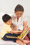 3 year old preschool age boy with grandmother looking at book read to