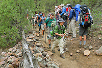 Photo story of Philmont Scout Ranch in Cimarron, New Mexico, taken during a Boy Scout Troop backpack trip in the summer of 2013. Photo is part of a comprehensive picture package which shows in-depth photography of a BSA Ventures crew on a trek. In this photo a BSA Venture Crew passes another crew as they head down the trail in the backcountry at Philmont Scout Ranch.   <br /> <br /> The  Photo by travel photograph: PatrickschneiderPhoto.com