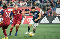 FOXBOROUGH, MA - SEPTEMBER 21: Carles Gil #22 of New England Revolution dribbles the ball as Erik Holt #20 of Real Salt Lake comes in to tackle during a game between Real Salt Lake and New England Revolution at Gillette Stadium on September 21, 2019 in Foxborough, Massachusetts.