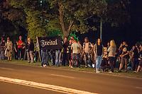 """Nach den pogromartigen Ausschreitungen gegen eine Fluechtlinsunterkunft im saechschen Heidenau am Freitag den 21. August 2015 durch Anwohnerinnen der Ortschaft, kamen am Samstag de 22. August 2015 ca. 250 Menschen in die Ortschaft um ihre Solidaritaet mit den Gefluechteten zu zeigen.<br /> Am Vorabend hatten Rassisten, Nazis und Hooligans sich zum Teil Strassenschlachten mit der Polizei geliefert um zu verhindern, dass Fluechtlinge in einen umgebauten Baumarkt einziehen. Ueber 30 Polizisten wurden dabei verletzt.<br /> Bis in die Abendstunden des 22. August blieb es trotz spuerbarer Anspannung um die Unterkunft ruhig. Im Laufe des Tages wurden immer wieder Gefluechtete mit Reisebussen gebracht was von den wartenenden Heidenauern mit Buh-Rufen begleitet wurde. Vereinzelt wurde auch """"Sieg Heil"""" gerufen, was die Polizei jedoch nicht verfolgte.<br /> Kurz vor 23 Uhr griffen Nazis und Hooligans wie am Vorabend die Polizei mit Steinen, Flaschen, Feuerwerkskoerpern und Baustellenmaterial an. Die Polizei mussten mehrfach den Rueckzug antreten, scheuchte den Mob dann von der Fluechtlingsunterkunft weg. Dabei wurden auch wieder Traenengasgranaten verschossen. Mindestens ein Nazi wurde festgenommen.<br /> Im Bild: Ein Rassist haelt eine Fahne """"Freital"""", einem 20 Km enfernter Ort, in dem auch Rassisten gewaltbereit gegen Gefluechtete vorgingen.<br /> 22.8.2015, Heidenau/Sachsen<br /> Copyright: Christian-Ditsch.de<br /> [Inhaltsveraendernde Manipulation des Fotos nur nach ausdruecklicher Genehmigung des Fotografen. Vereinbarungen ueber Abtretung von Persoenlichkeitsrechten/Model Release der abgebildeten Person/Personen liegen nicht vor. NO MODEL RELEASE! Nur fuer Redaktionelle Zwecke. Don't publish without copyright Christian-Ditsch.de, Veroeffentlichung nur mit Fotografennennung, sowie gegen Honorar, MwSt. und Beleg. Konto: I N G - D i B a, IBAN DE58500105175400192269, BIC INGDDEFFXXX, Kontakt: post@christian-ditsch.de<br /> Bei der Bearbeitung der Dateiinformationen darf die """