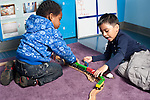 Education Preschool two boys playing together with train set and wooden track