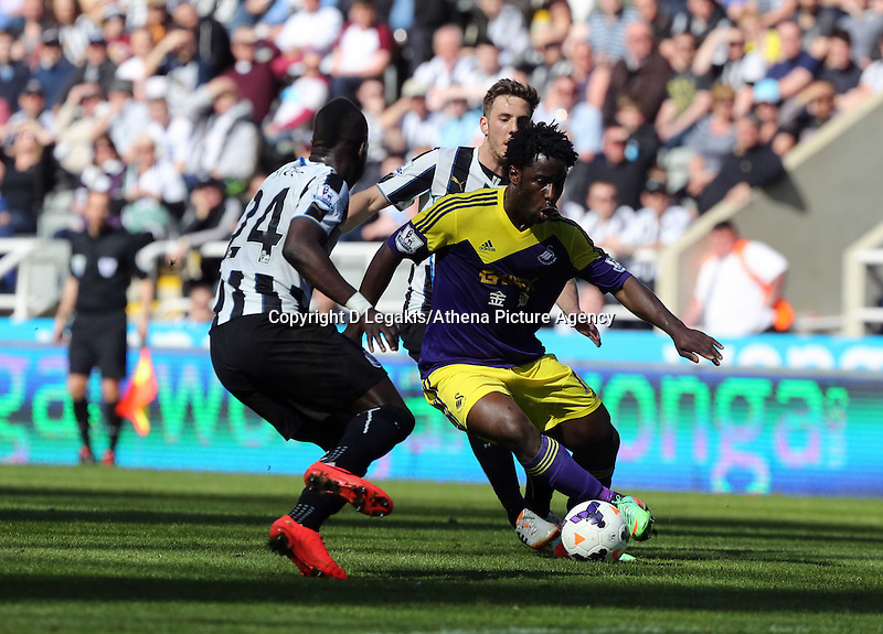 Pictured: Wilfried Bony of Swansea (R) gets past Cheik Tiote (L) of Newcastle. . Saturday 19 April 2014<br /> Re: Barclay's Premier League, Newcastle United v Swansea City FC at St James Park, Newcastle, UK.