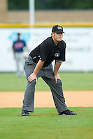 Umpire Richard Riley handles the calls on the bases during the Appalachian League game between the Elizabethton Twins and the Burlington Royals at Burlington Athletic Park on August 11, 2013 in Burlington, North Carolina.  The Twins defeated the Royals 12-5.  (Brian Westerholt/Four Seam Images)