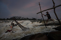 A fishermen, stands in a torrent of water as he checks a fish trap attached to a wooden scaffold at Boyoma Falls (known locally as Wagenia Falls). This is the last of seven cataracts below which the Lualaba River becomes the Congo. For generations members of the Wagenia tribe have built and maintained these structures in the same manner described by Henry Morton Stanley, after whom the falls were also once named, during his navigation of the Congo in 1874-77.