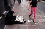 """Economic Turmoil in Argentina<br /> There are 36 million people living in Argentina. According to government figures 21 million of the population fall are official poor or very poor. An elderly woman begs, her sign says that she has """".. .4 children, her husband is out of work"""" 2000s 2002"""