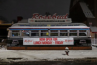 """Despite a banner reading """"Now open for lunch Monday-Friday,"""" Rosebud American Kitchen & Bar, a high-end diner in Davis Square, is temporarily closed in hibernation due to the ongoing Coronavirus (COVID-19) global pandemic in Davis Square in Somerville, Massachusetts, on Tue., Jan. 26, 2021. On Dec. 27, 2020, the restaurant announced the closure on Instagram, reading, in part: """"It's with heavy hearts that we announce today is our last RoseBrunch for a while. We're making the very difficult & heartbreaking decision to close our diner doors & turn off our neon for the winter....We aren't calling this a hibernation because that feels cute & natural and this is anything but that. We need aid & relief from our city & government that we just aren't getting right now.""""<br /> <br /> The vintage neon sign is normally a fixture in the area at night, but it has been turned off since Dec. 27."""