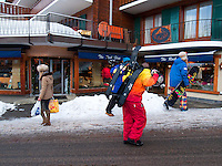 Switzerland. Canton Valais. Verbier is a village located in the municipality of Bagnes. The village lies on a south orientated terrace at around 1,500 metres. The terrace lies on the east side of the Val de Bagnes. Shopping. The rock shop. A woman carries her groceries while a group of young men carry a snowboard and their sledges. Verbier had 3000 permanent residents in 2010. The number of residents can rise to 35,000 in the winter season. Verbier is one of the largest holiday resort and ski areas in the Swiss Alps. 4.01.2012 © 2012 Didier Ruef