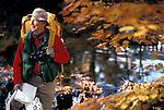 happy healthy elderly man hiking in autmn woods