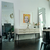 """A bright note of yellow is struck by an Andy Warhol """"Marilyn"""" screenprint hanging between two full-length mirrors in the black-and-white dining room of this New York town house"""