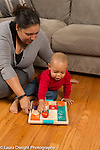 18 month old toddler boy with mother playing with new toy ball and wooden maze, mother holding board to help