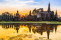 Wat Maha That temple and Buddha statue sunrise and beautiful pond reflections in famous Sukhothai Historical Park, Thailand, Southeast Asia