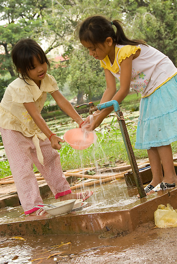 Two young Cambodian girls wash their dishes outside of the Artisans D'Angkor.  The Artisans D'Angkor  was established as a work place for young artists schooled through the Chantiers-Ecoles de Fomations Professionnelle which was a school founded to help Cambodians rediscover traditional handicrafts.