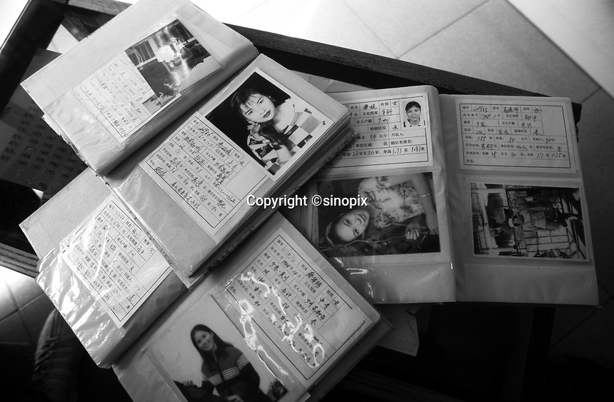 Books of women for potential brides at the Heart to Heart Dating Agency in Guangzhou, China. An average gender inbalance 120 males to 100 females caused by the Chinese Governments One Child Policy and the  preference for boys means that there is a shortage of women brides in China with men increasingly looking to matching agencies to find a bride.<br /> May 2000<br /> <br /> photo by Richard Jones / Sinopix