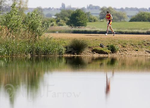 10 MAY 2009 - GRENDON,GBR - Team Cherwells Mark Jackson checks his watch during the run - Grendon Triathlon .(PHOTO (C) NIGEL FARROW)