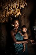 Mahari Usenti is seen with her little child inside her hut in Godhari village in Orcha block of Chattisgarh, India. Photo: Sanjit Das