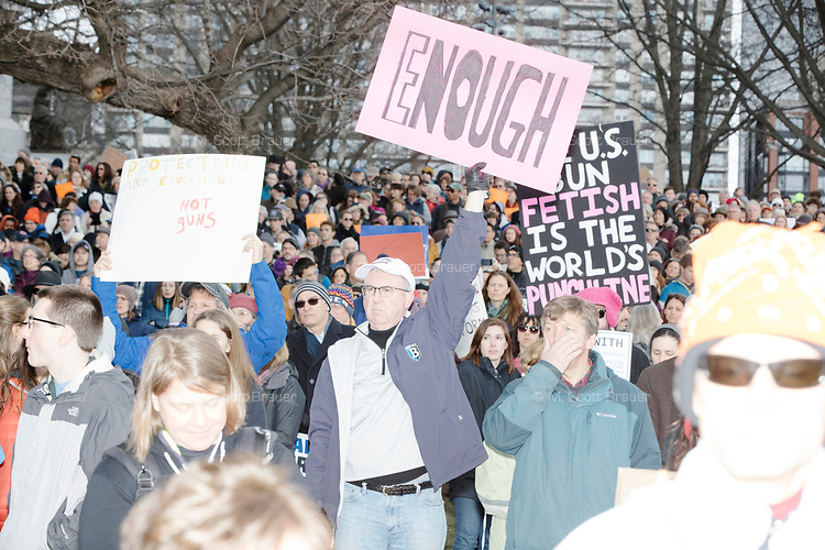 """A man holds a sign reading """"Enough"""" as people gather during the March For Our Lives protest and demonstration in Boston Common in Boston, Massachusetts, USA, on Sat., March 24, 2018. The march was held in response to recent school gun violence."""