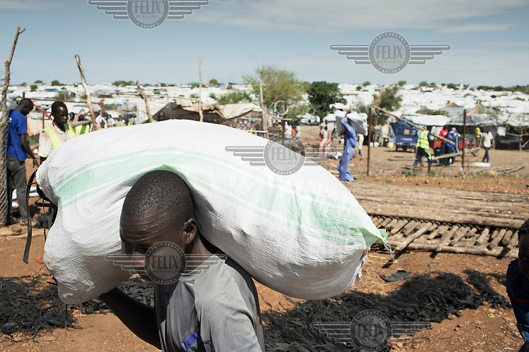 A man carries a sack of rice into an UN protection of civilians (PoC) camp near Juba.