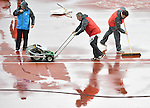 Officials clear water off the track before women's pole vault competition can start<br /> <br /> Photographer Chris Vaughan/CameraSport<br /> <br /> 20th Commonwealth Games - Day 10 - Saturday 2nd August 2014 - Athletics - Hampden Park - Glasgow - UK