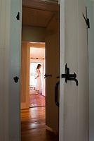 Woman wearing negligee standing in bathroom<br />