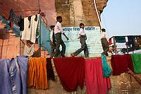27.11.2008 Varanasi(Uttar Pradesh)<br /> <br /> School boys walking in the ghat with linen of pilgrims drying around.<br /> <br /> Ecoliers marchant sur le ghat avec du linge des pélerins en train de sécher autour.