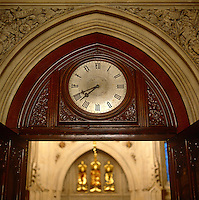 An engraved clock is recessed into the wooden carved panelling above a doorway