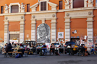 Students studying in front of cinema Palazzo, an occupied cinema that was cleared out some days ago by the Police. The university students decided to protest taking desks and computers in the square just in front of the cinema and studying there to keep the place 'occupied'. In the background a painting by the street artist Sten Lex.<br /> Rome (Italy), November 30th 2020<br /> Photo Samantha Zucchi Insidefoto