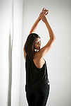Young Hispanic woman with arms raised